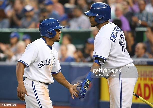 Ben Revere of the Toronto Blue Jays is congratulated by Edwin Encarnacion after scoring a run in the fifth inning during MLB game action against the...