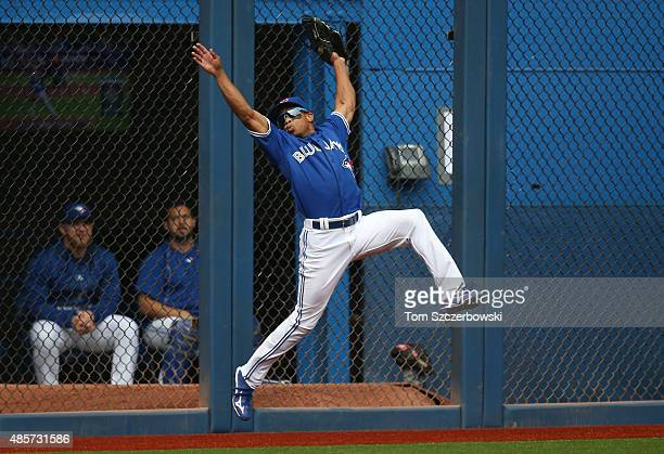 Ben Revere of the Toronto Blue Jays makes a catch against the wall in the first inning during MLB game action against the Detroit Tigers on August 29...