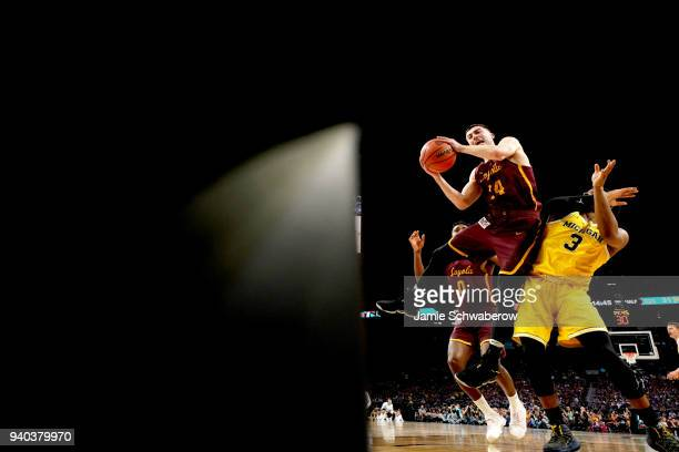 Ben Richardson of the Loyola Ramblers attempts a shot defended by Zavier Simpson of the Michigan Wolverines in the 2018 NCAA Photos via Getty Images...