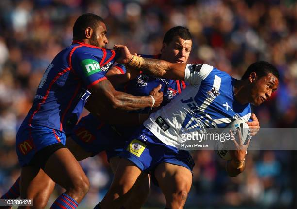 Ben Roberts of the Bulldogs is tackled by Wes Naiqama and Jarrod Mullen of the Knights during the round 22 NRL match between the Newcastle Knights...