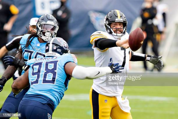 Ben Roethlisberger of the Pittsburgh Steelers throws a shuffle pass in the first half while under pressure from Jeffery Simmons of the Tennessee...