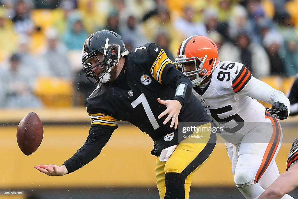 Ben Roethlisburgher #7 of the Pittsburgh Steelers juggles the ball as he is hit by Armonty Bryant #95 of the Cleveland Browns during the game at Heinz Field on December 29, 2013 in Pittsburgh, Pennsylvania. The Steelers defeated the Browns 20-7.