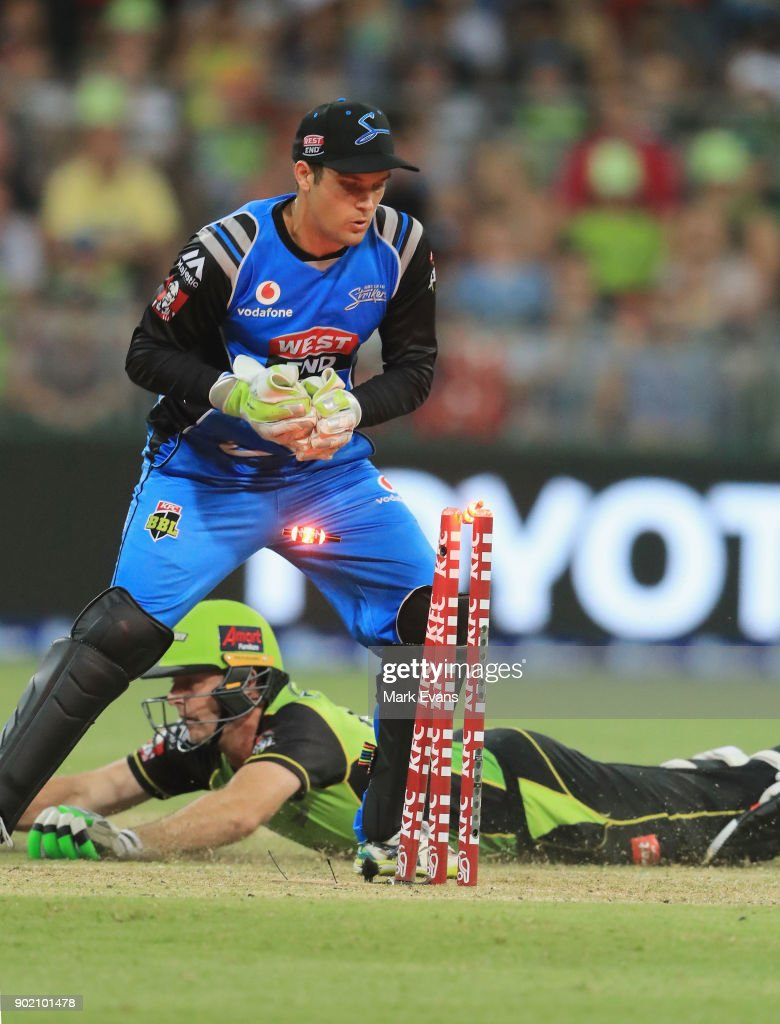 Ben Rohrer of Thunder slides into the crease as Alex Carey of the Strikers knocks the bails off during the Big Bash League match between the Sydney Thunder and the Adelaide Strikers at Spotless Stadium on January 7, 2018 in Sydney, Australia.