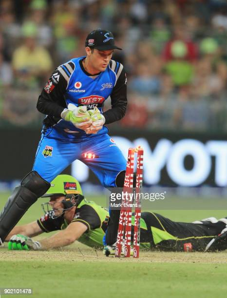 Ben Rohrer of Thunder slides into the crease as Alex Carey of the Strikers knocks the bails off during the Big Bash League match between the Sydney...