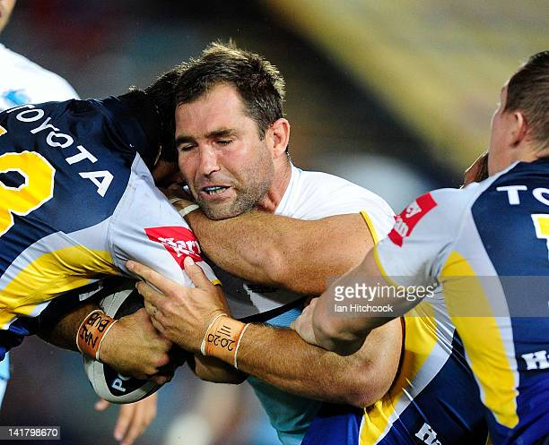 Ben Ross of the Sharks is tackled by Dallas Johnson and Glenn Hall of the Cowboys during the round four NRL match between the North Queensland...