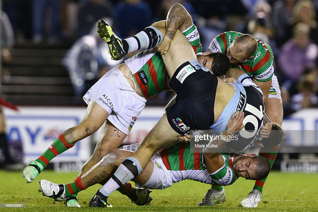 Ben Ross of the Sharks is tackled during the round 11 NRL match between the Cronulla Sharks and the South Sydney Rabbitohs at Sharks Stadium on May 27, 2013 in Sydney, Australia.
