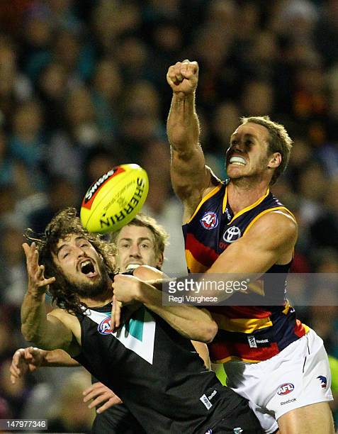 Ben Rutten of the Crows punches the ball away from John Butcher of the Power during the round 15 AFL match between the Port Adelaide Power and the...