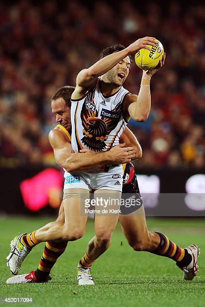 Ben Rutten of the Crows tackles Jordan Lewis of the Hawks during the round 17 AFL match between the Adelaide Crows and the Hawthorn Hawks at Adelaide...