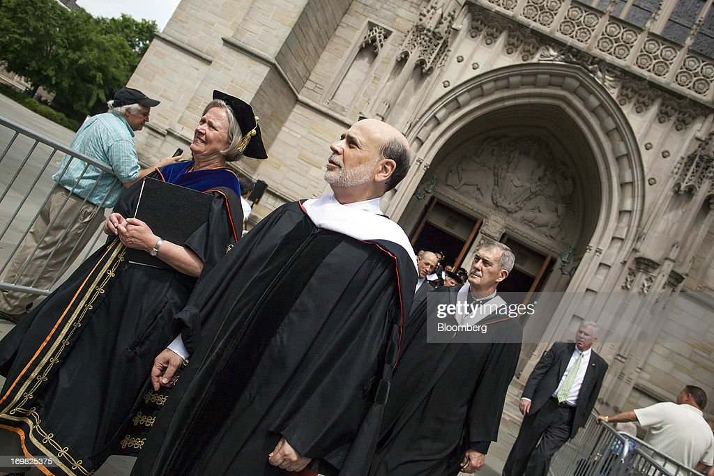 Ben S. Bernanke, chairman of the U.S. Federal Reserve, center, walks in a processional with Shirley Tilghman, president of Princeton University, first from left, after delivering the commencement speech to graduates at Princeton University in Princeton, New Jersey, U.S., on Sunday, June 2, 2013. Bernanke, returning to the Princeton University campus where he taught economics for 17 years, offered graduating seniors often humorous advice on subjects ranging from love and success to money and politics in a speech that quoted St. Luke, Lily Tomlin and Forrest Gump. Photographer: Michael Nagle/Bloomberg via Getty Images