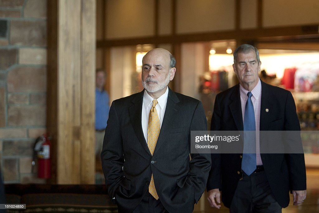 Ben S. Bernanke, chairman of the U.S. Federal Reserve, left, arrives for an opening dinner and reception at an economic symposium sponsored by the Kansas City Federal Reserve Bank at the Jackson Lake Lodge in Moran, Wyoming, U.S., on Thursday, Aug. 30, 2012. Bernanke, who last month said a third asset-purchase program was an option, has an opportunity to update his policy outlook tomorrow in a speech to the Kansas City Fed's annual symposium. Photographer: Travis J. Garner/Bloomberg via Getty Images