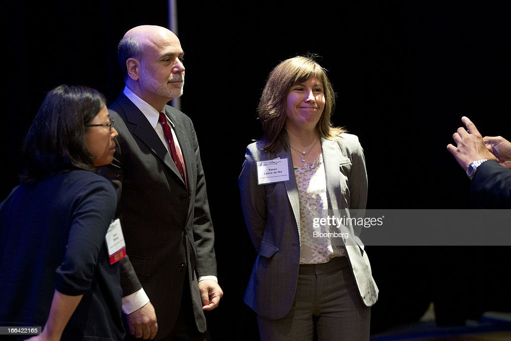Ben S. Bernanke, chairman of the U.S. Federal Reserve, second from left, has his photograph taken with attendees at a community development research conference sponsored by the Federal Reserve in Washington, D.C., U.S., on Friday, April 12, 2013. Bernanke said aiding low-income neighborhoods requires a 'multipronged' approach focusing on education, jobs and health care as well as housing. Photographer: Andrew Harrer/Bloomberg via Getty Images