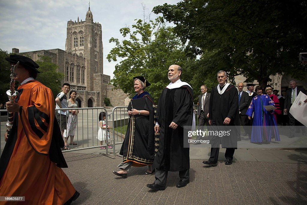 Ben S. Bernanke, chairman of the U.S. Federal Reserve, third from left, walks in a processional with Shirley Tilghman, president of Princeton University, second from left, and Jeff Nunokawa, professor of English and master of Rockefeller College, first from left, after delivering the commencement speech to graduates at Princeton University in Princeton, New Jersey, U.S., on Sunday, June 2, 2013. Bernanke, returning to the Princeton University campus where he taught economics for 17 years, offered graduating seniors often humorous advice on subjects ranging from love and success to money and politics in a speech that quoted St. Luke, Lily Tomlin and Forrest Gump. Photographer: Michael Nagle/Bloomberg via Getty Images
