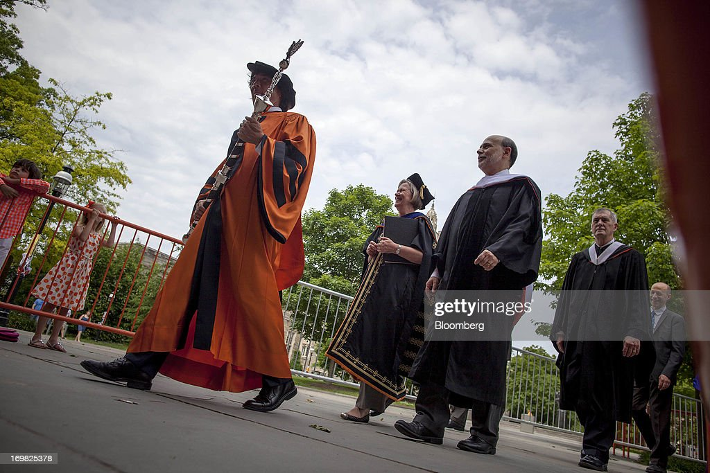 Ben S. Bernanke, chairman of the U.S. Federal Reserve, third from left, walks in a processional with Shirley Tilghman, president of Princeton University, center, and Jeff Nunokawa, professor of English and master of Rockefeller College, first from left, after delivering the commencement speech to graduates at Princeton University in Princeton, New Jersey, U.S., on Sunday, June 2, 2013. Bernanke, returning to the Princeton University campus where he taught economics for 17 years, offered graduating seniors often humorous advice on subjects ranging from love and success to money and politics in a speech that quoted St. Luke, Lily Tomlin and Forrest Gump. Photographer: Michael Nagle/Bloomberg via Getty Images