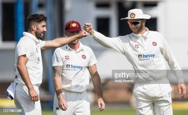 Ben Sanderson of Northamptonshire celebrates with his team mate Rob Keogh after taking the wicket of Jamie Overton of Somerset , his fifth of the...