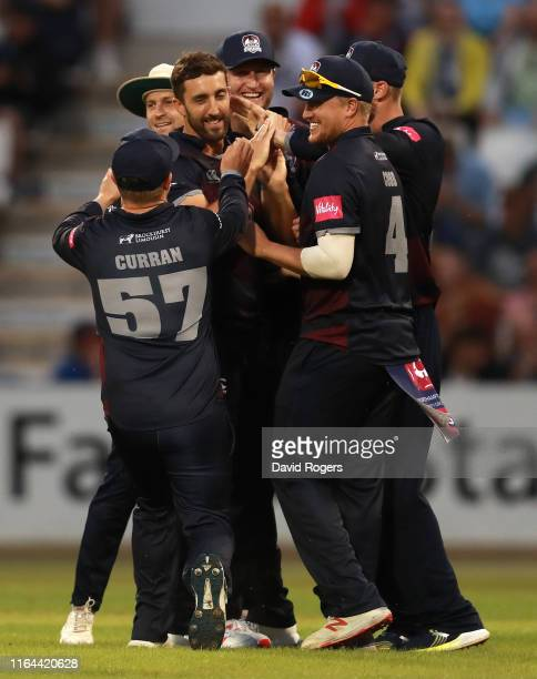 Ben Sanderson of Northamptonshire is mobbed by team mates after taking the wicket of Ed Pollock during the Vitality Blast match between...