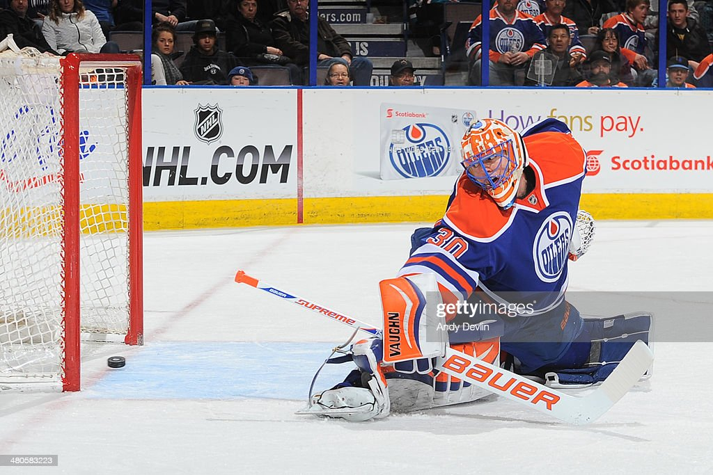 Ben Scrivens #30 of the Edmonton Oilers looks back as the puck crosses the goal line in a game against the San Jose Sharks on March 25, 2014 at Rexall Place in Edmonton, Alberta, Canada.