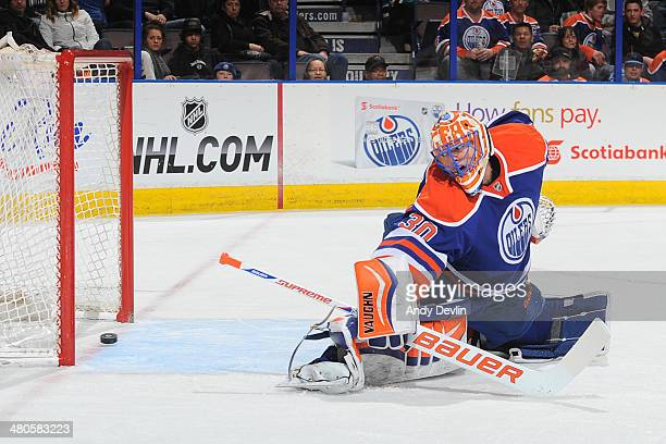 Ben Scrivens of the Edmonton Oilers looks back as the puck crosses the goal line in a game against the San Jose Sharks on March 25 2014 at Rexall...
