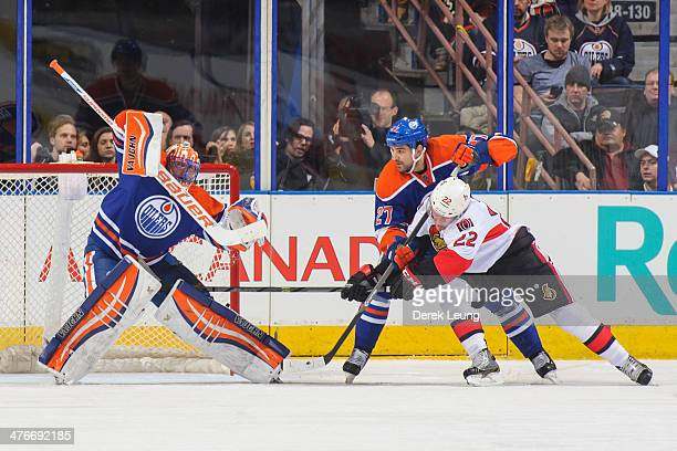 Ben Scrivens of the Edmonton Oilers stops a shot in front of Erik Condra of the Ottawa Senators during an NHL game at Rexall Place on March 04 2014...
