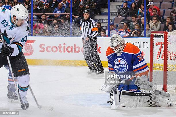 Ben Scrivens of the Edmonton Oilers stops the shot of Matt Nieto of the San Jose Sharks during an NHL game at Rexall Place on January 29 2014 in...