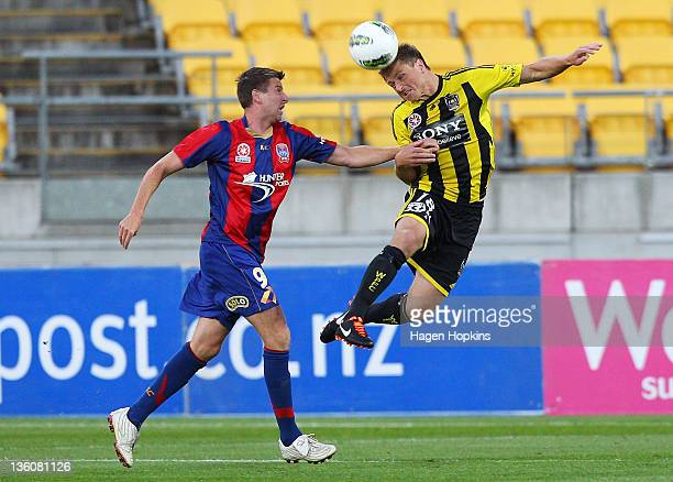 Ben Sigmund of the Phoenix heads the ball while Michael Bridges of the Jets looks on during the round 12 ALeague match between Wellington Phoenix and...