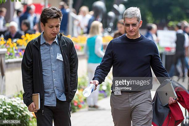 Ben Silbermann cofounder and chief executive officer of Pinterest Inc left and Tim Cook chief executive officer of Apple Inc talk as they walk the...