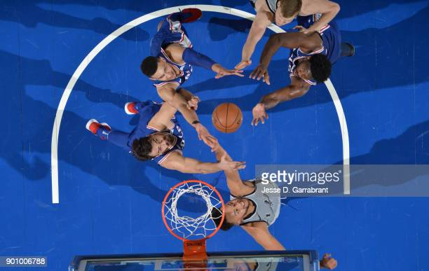 Ben Simmons and Joel Embiid and Dario Saric of the Philadelphia 76ers grab a rebound against the San Antonio Spurs at Wells Fargo Center on January 3...