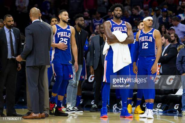 Ben Simmons Joel Embiid and Tobias Harris of the Philadelphia 76ers look on after Joel Embiid got into a fight with KarlAnthony Towns of the...
