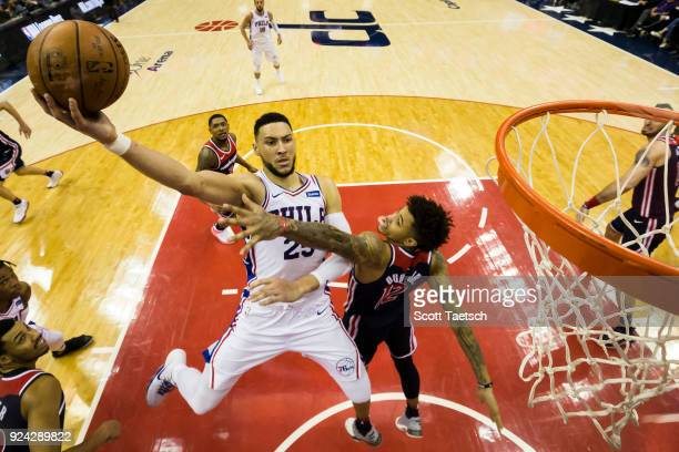 Ben Simmons of the Philadelphia 76ers dunks over Kelly Oubre Jr #12 of the Washington Wizards during the second half at Capital One Arena on February...