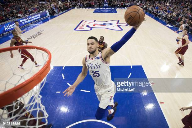 Ben Simmons of the Philadelphia 76ers dunks the ball past LeBron James of the Cleveland Cavaliers in the second quarter at the Wells Fargo Center on...