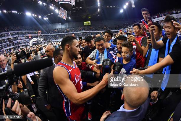 Ben Simmons of the Philadelphia 76ers gives his sneakers to a fan at the end of the game as part of the 2018 NBA China Games on October 8 2018 at the...