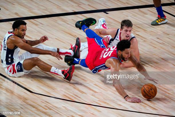 Ben Simmons of the Philadelphia 76ers goes for a loose ball with Jerome Robinson and Moritz Wagner of the Washington Wizards during the first half of...
