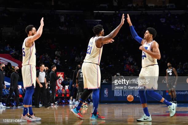 Ben Simmons of the Philadelphia 76ers, Joel Embiid of the Philadelphia 76ers, and Tobias Harris of the Philadelphia 76ers high-five during a game...