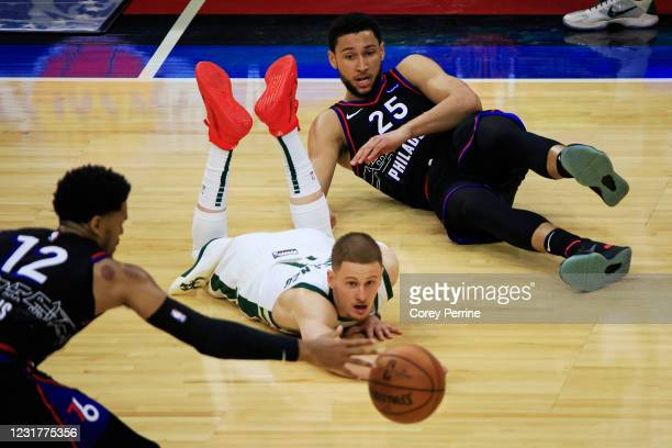 Ben Simmons of the Philadelphia 76ers passes against Donte DiVincenzo of the Milwaukee Bucks to Sixers teammate Tobias Harris during the second...