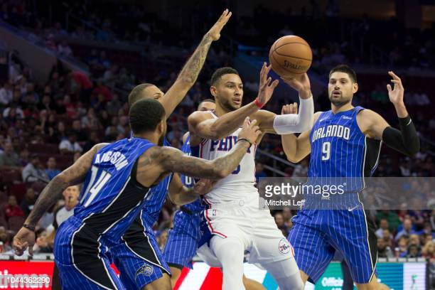 Ben Simmons of the Philadelphia 76ers passes the ball against DJ Augustin Evan Fournier and Nikola Vucevic of the Orlando Magic during the first...