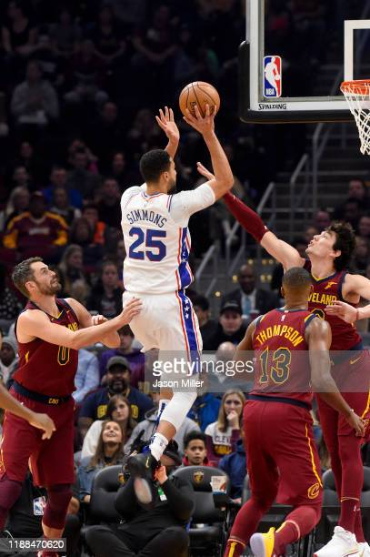 Ben Simmons of the Philadelphia 76ers shoots over Kevin Love Tristan Thompson and Cedi Osman of the Cleveland Cavaliers during the first half at...