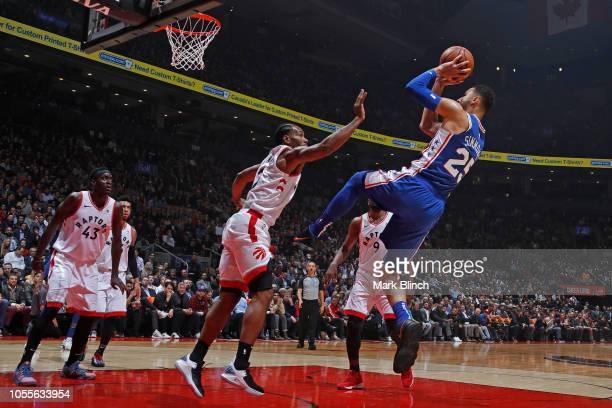 Ben Simmons of the Philadelphia 76ers shoots the ball over Kawhi Leonard of the Toronto Raptors on October 30 2018 at Soctiabank Arena in Toronto...