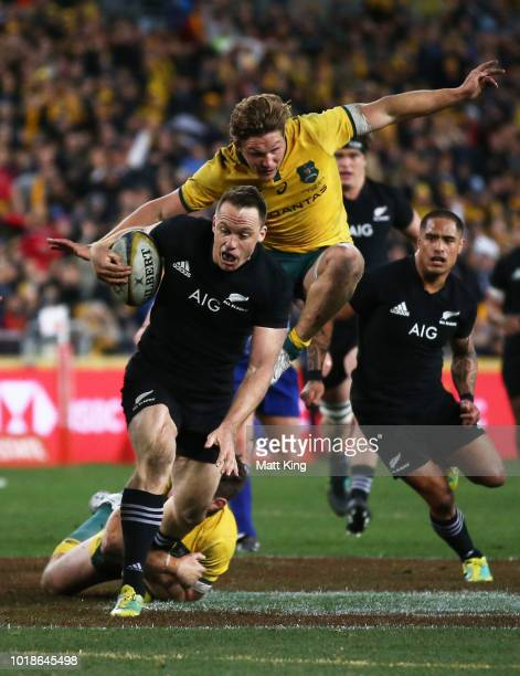 Ben Smith of the All Blacks is tackled as Michael Hooper of the Wallabies jumps in the background during The Rugby Championship Bledisloe Cup match...