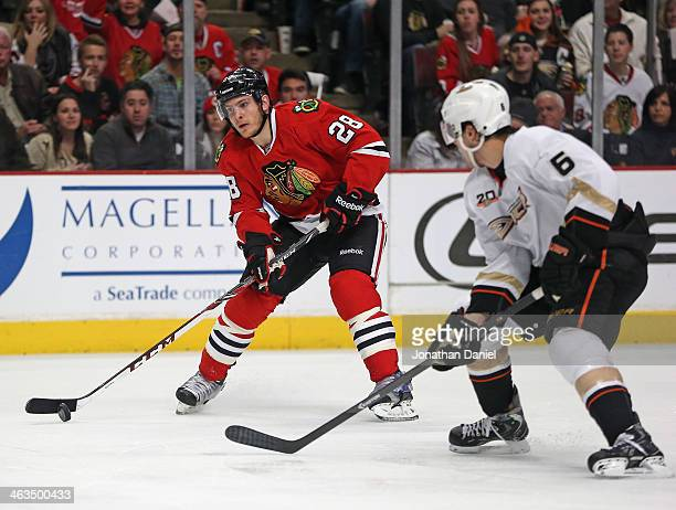 Ben Smith of the Chicago Blackhawks challenges Ben Lovejoy of the Anaheim Ducks at the United Center on January 17 2014 in Chicago Illinois The...