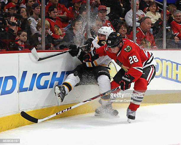 Ben Smith of the Chicago Blackhawks checks Torey Krug of the Boston Bruins as they battle for the puck at the United Center on January 19 2014 in...