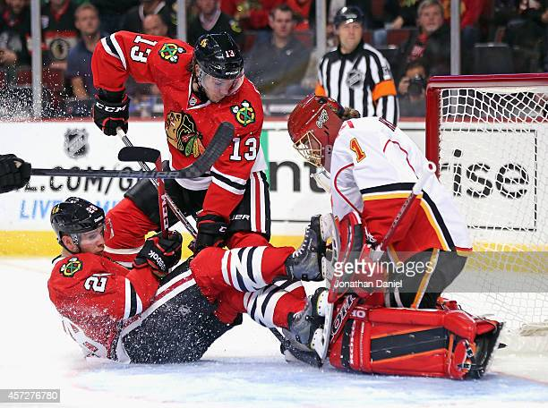 Ben Smith of the Chicago Blackhawks collides with Jonas Hiller of the Calgary Flames as Daniel Carcillo tries to dig out the puck at the United...