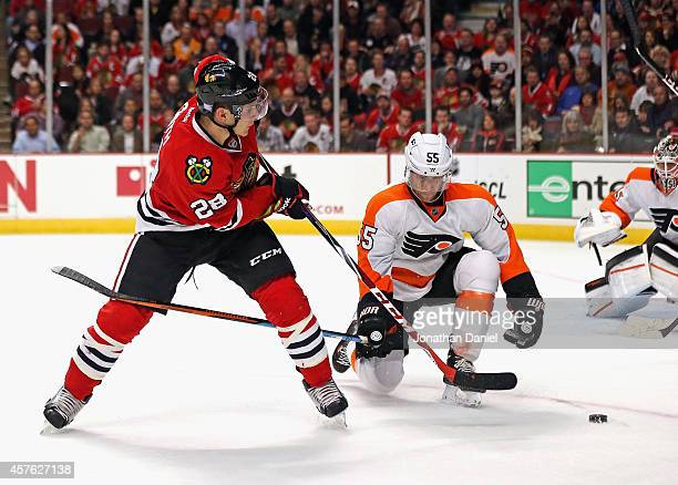 Ben Smith of the Chicago Blackhawks fires a shot under pressure from Nick Schultz of the Philadelphia Flyers at the United Center on October 21, 2014...