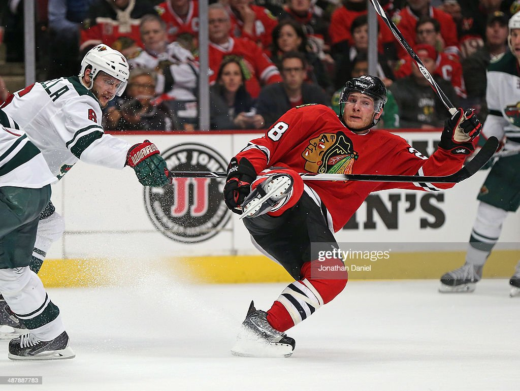 Ben Smith #28 of the Chicago Blackhawks keeps his balance after colliding with Marco Scandella #6 of the Minnesota Wild in Game One of the Second Round of the 2014 NHL Stanley Cup Playoffs at the United Center on May 2, 2014 in Chicago, Illinois.