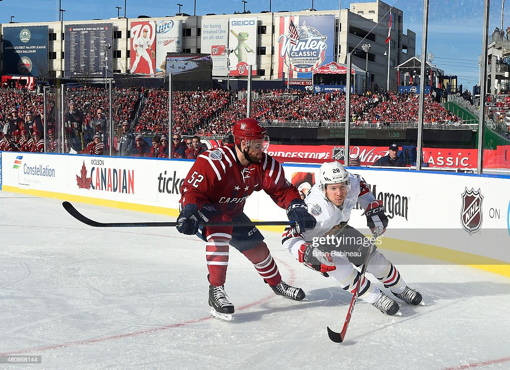 Ben Smith #28 of the Chicago Blackhawks skates around Mike Green #52 of the Washington Capitals in the corner during the first period of the 2015 Bridgestone NHL Winter Classic at Nationals Park on January 1, 2015 in Washington, D.C.
