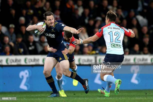 Ben Smith of the Highlanders fends off David Horwitz of the Waratahs during the round 14 Super Rugby match between the Highlanders and the Waratahs...