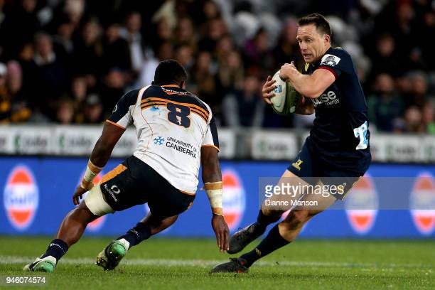 Ben Smith of the Highlanders is challenged by Isi Naisarani of the Brumbies during the round nine Super Rugby match between the Highlanders and the...