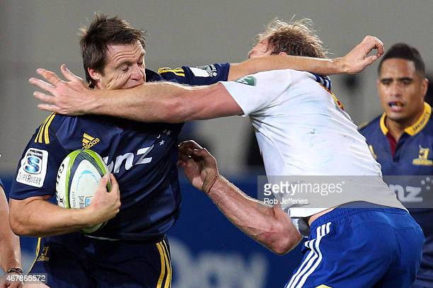 Ben Smith of the Highlanders is hit in a high tackle by Schalk Burger during the round seven Super Rugby match between the Highlanders and the...