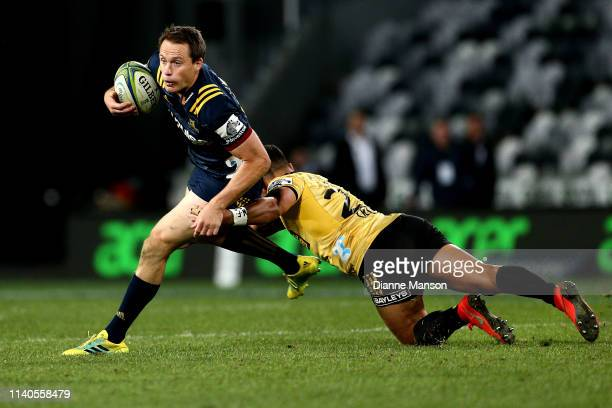 Ben Smith of the Highlanders is tackled by Matt Proctor of the Hurricanes during the round 8 Super Rugby match between the Highlanders and Hurricanes...