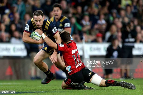 Ben Smith of the Highlanders is tackled by Mitchell Hunt of the Crusaders during the round five Super Rugby match between the Highlanders and the...