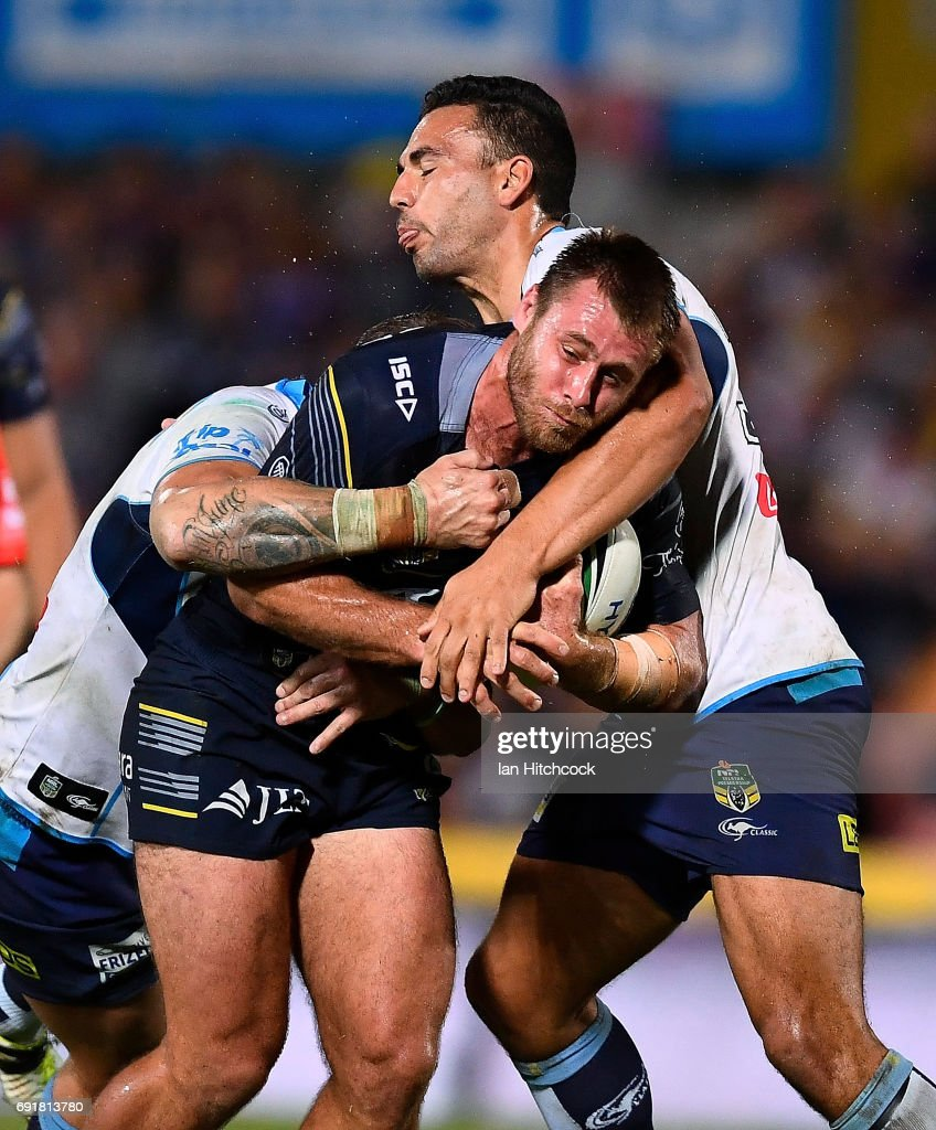 Ben Spina of the Cowboys is tackled by Ryan James of the Titans during the round 13 NRL match between the North Queensland Cowboys and the Gold Coast Titans at 1300SMILES Stadium on June 3, 2017 in Townsville, Australia.