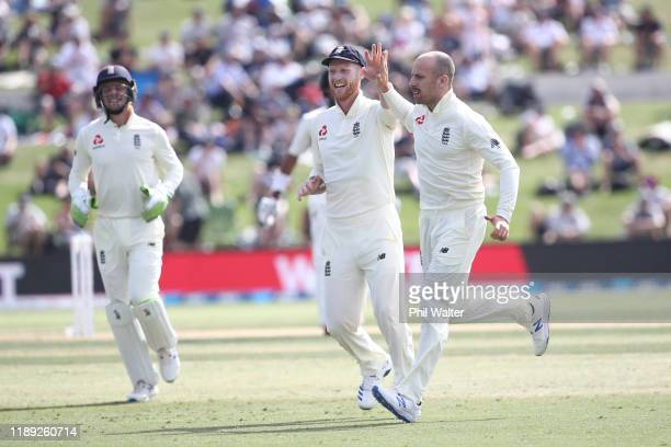 Ben Stokes and Jack Leach of England celebrate the wicket of Jeet Raval of New Zealand during day two of the first Test match between New Zealand and...